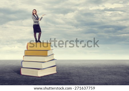 Successful young woman standing on top of the foot pointing to the books free space for your Publicity.