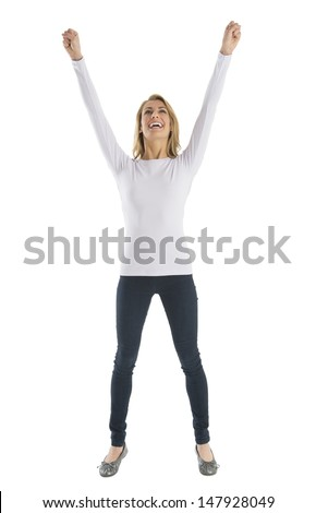 Successful young woman with arms raised looking up while standing against white background - stock photo