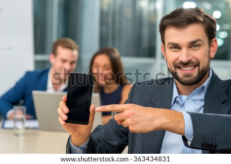 Successful young working team is discussing project. They are sitting at the table in office. The man and woman are looking at notebook. The businessman is showing mobile phone and smiling