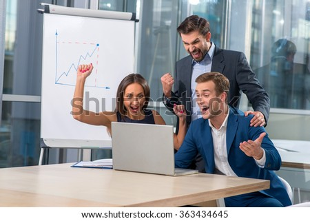 Successful young working team made a deal a customer. They are looking at the notebook and laughing. The business partners are gesturing happily - stock photo