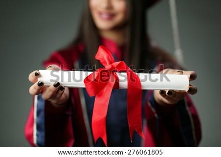 successfully graduated girl handing hers degree - stock photo