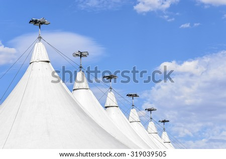 Succession of white big tops, with spotlights over them. Sunny day with blue sky and some clouds - stock photo