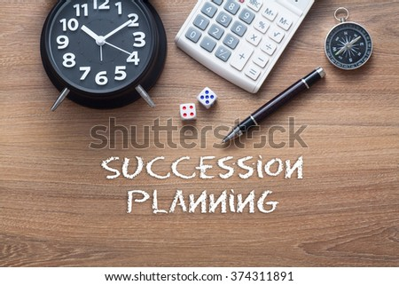 Succession planning written on wooden table with clock,dice,calculator pen and compass - stock photo