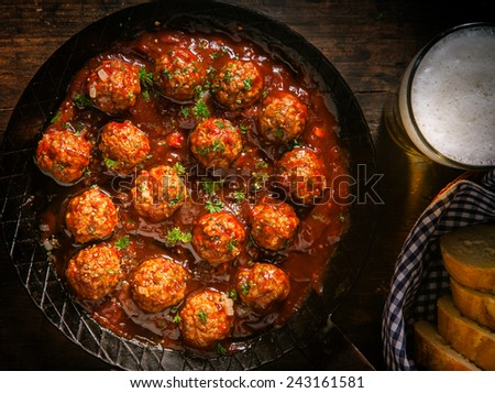 Succulent beef meatballs in a spicy tomato sauce garnished with fresh aromatic herbs served with a glass of beer and bread, close up overhead view - stock photo