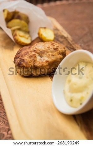 Succulent cooked beef burger with potato on a wood plate. - stock photo