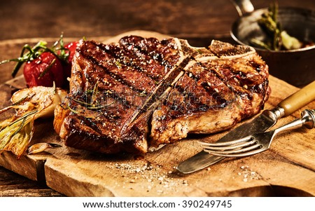 Succulent grilled large t-bone steak garnished with herbs, tomato and salt with fork and knife beside it on cutting board - stock photo