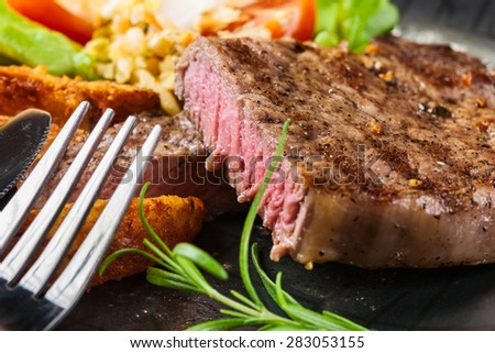 Succulent portion of beef steak served with roast potatoes - stock photo