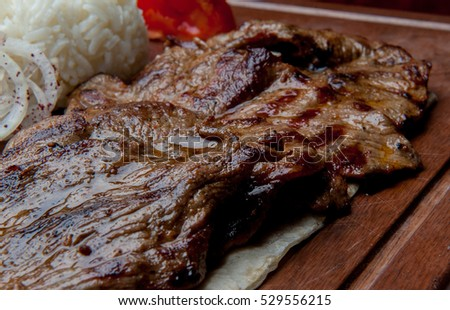 Succulent thick juicy portions of grilled fillet steak served with tomatoe and roast vegetables on wooden board. Tender grilled porterhouse or t-bone steakwith crisp golden French fries. BBQ or tomato