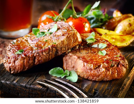 Succulent thick juicy portions of grilled fillet steak served with tomatoes and roast vegetables on an old wooden board - stock photo