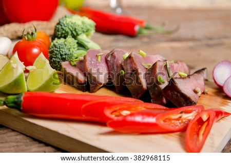 Succulent thick juicy portions of grilled fillet steak served with tomatoes and roast vegetables on an wooden board