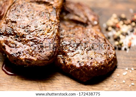 Succulent thick juicy portions of grilled steaks on an old wooden board with salt and pepper - stock photo