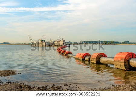 Suction dredger in a Dutch river sucks sand and gravel from the river bottom and transports it via a floating pipeline with orange floats to the shore. - stock photo