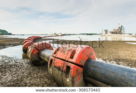 Suction dredger in a river sucks sand and gravel from the river bottom and transports it via a floating pipeline with orange floats to the shore. - stock photo