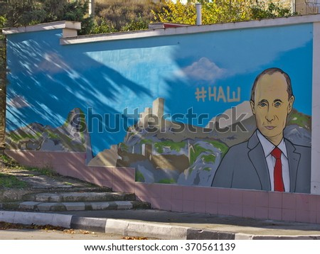 SUDAK, CRIMEA, RUSSIA - NOVEMBER, 11 2015: Street art on wall Russia`s President Vladimir Putin with hashtag #our (nash) on the background of symbol of the city - the Genoese fortress in Crimea - stock photo