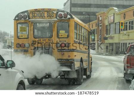 Sudbury, Ontario, Canada February 15th 2014. School bus in traffic on a snowy Canadian street at -38 Celsius or -36.4 Fahrenheit Image taken on February 15th 2014 on Paris st, Sudbury Ontario, Canada  - stock photo
