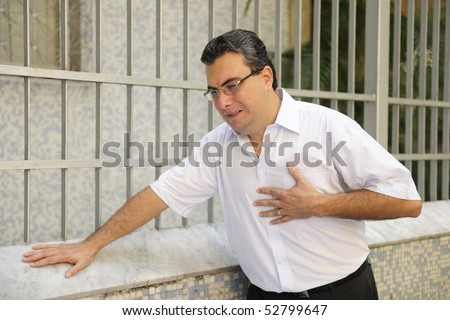Sudden chest pain: Man having a heart attack bending - stock photo