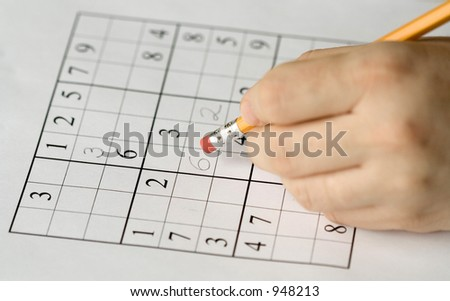 sudoku puzzle and hand erasing, focus on mistake - stock photo