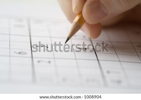 sudoku puzzle and hand holding pencil - stock photo