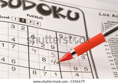 Sudoku puzzle in newspaper being solved with a red pen.
