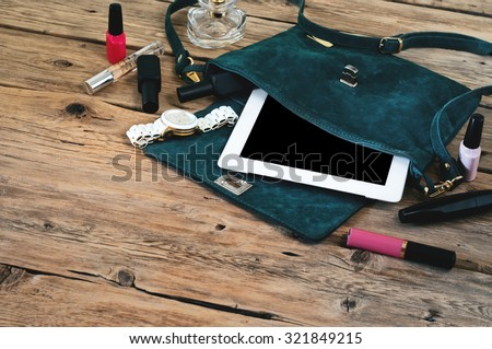 Suede womens bag with tablet computer, watch and women cosmetics (lip gloss, mascara, nail polish and spirits)  on a wooden table closeup. Top view - stock photo
