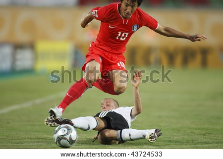 SUEZ, EGYPT - SEPTEMBER 29:  Young Cheol Cho of the Korea Republic (10) leaps over a tackle during a FIFA U-20 World Cup soccer match against Germany  September 29, 2009 in Suez, Egypt. - stock photo