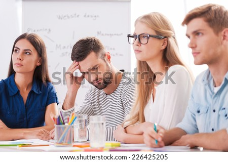 Suffering from awful headache. Depressed young man touching head with hand while sitting at the table together with his colleagues  - stock photo