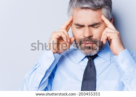 Suffering from headache. Depressed mature man in shirt and tie touching head with fingers and keeping eyes closed while standing against grey background - stock photo