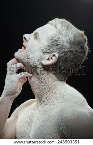 Suffering from itchy skin. Conceptual closeup portrait of angry shirtless man scratching his face and neck while covered with white powder on dark background - stock photo