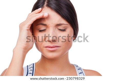 Suffering from migraine. Depressed young woman holding a hand on forehead while standing against white background   - stock photo