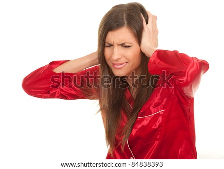 suffering from  pain - young woman in red pajamas with headache, hands on head - stock photo