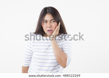Suffering from toothache. Frustrated young woman touching her cheek and standing isolated on white background