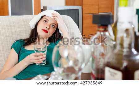 Suffering girl having headache after celebrating of holiday - stock photo