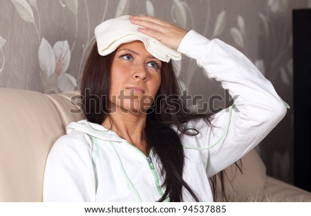 Suffering girl stupes  towel to her head - stock photo