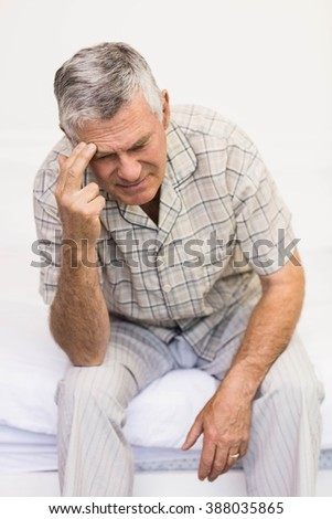 Suffering senior man touching his forehead at home