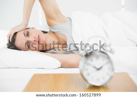 Suffering young woman lying on her bed touching her head looking seriously at camera - stock photo