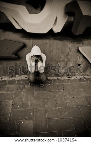 Suffering young woman on urban scenery. Hard sepia toned with vignetting. - stock photo