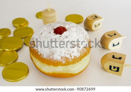 Sufganiya , Doughnut , with dreidel (spinning top), gelts (candy coins) for the Jewish holiday of Hanukkah. - stock photo