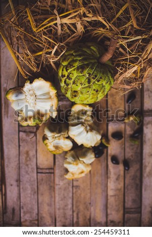 Sugar apple - cherimoya ( Annona scaly ) on the board with hay with bones and a plate - stock photo