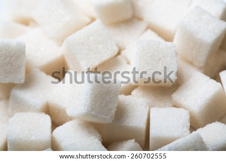 Sugar background sweet food ingredient with a close up of a pile of delicious white lumps of cubes as a symbol of cooking and baking and the diet health risks related to diabetes and calorie intake. - stock photo