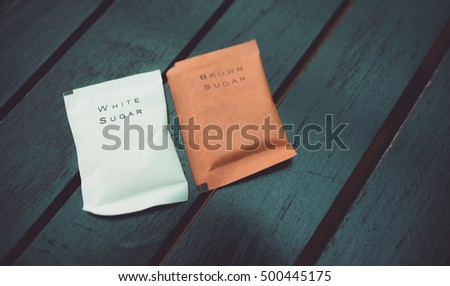 sugar bags,white sugar and brown sugar on wooden table.