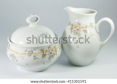 sugar bowl and milk jug with flowers on a white background