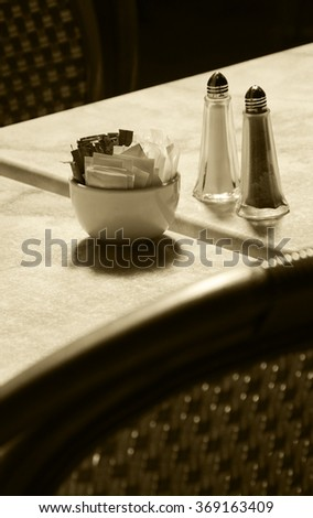 Sugar bowl with brown and white sugar sachets, salt cellar and pepper caster on marble table at an outdoor cafe. Wicker chairs. Selective focus on the sugar bowl. Aged photo. Sepia. - stock photo