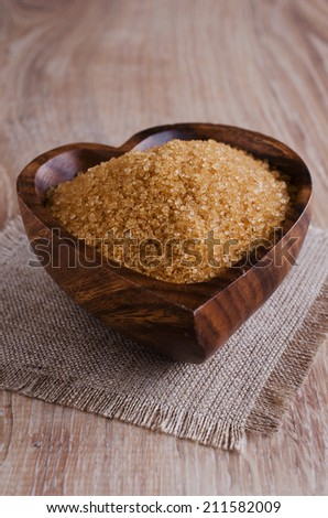 Sugar brown, lying in a wooden bowl - stock photo