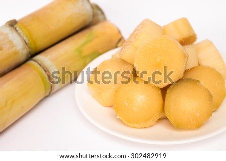 Sugar cane and peel pieces stack on dish - stock photo