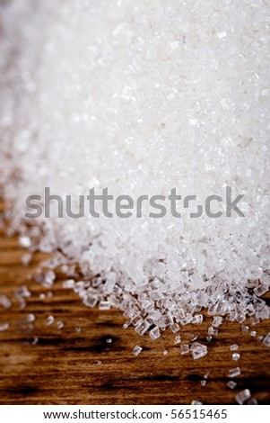 sugar closeup on wooden background - stock photo