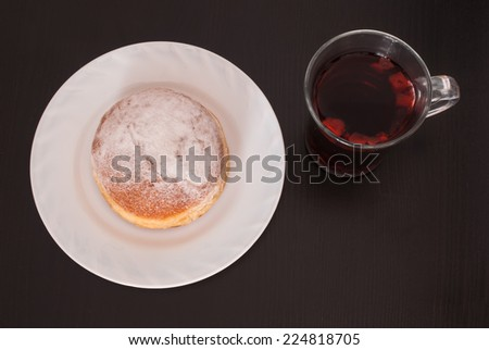 Sugar coated donut and a glass of fruit tea on black wooden background - stock photo