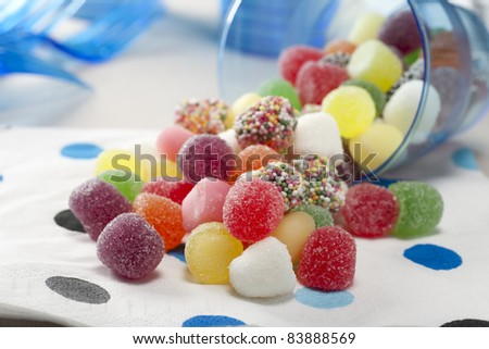 Sugar coated jelly candies spilling from a cup