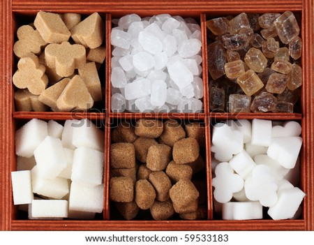 Sugar collection - various kinds of sugar cubes and candies in a box. Shallow dof - stock photo