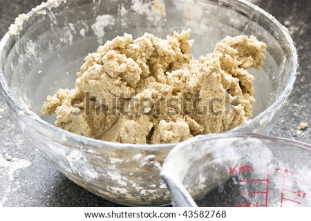 Sugar cookie dough in a glass bowl with measuring cup in front (focus on bowl) - stock photo
