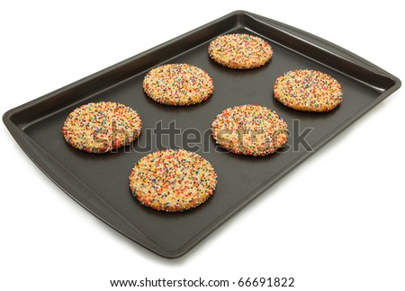 Sugar Cookies With Colorful Sprinkles On Baking Sheet Over White Background - stock photo